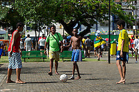 Kids play football in front of the Arena Fonte Nova
