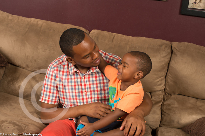 Three year old boy at home sitting with father on couch talking