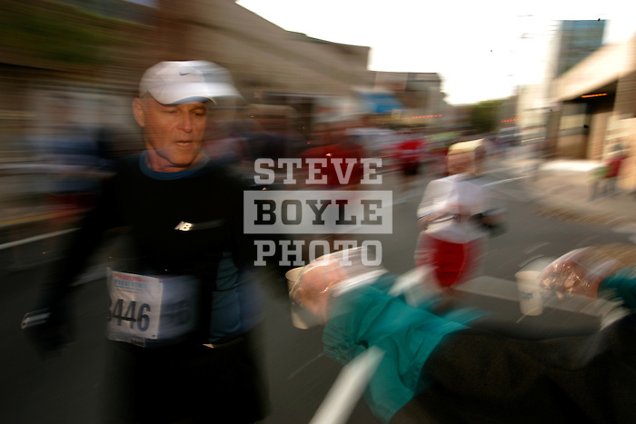 Martin Faigus (65) grabs a cup of water at a water station on Sixth Street during the Philadelphia Marathon in Philadelphia, Pennsylvania on November 19, 2006.