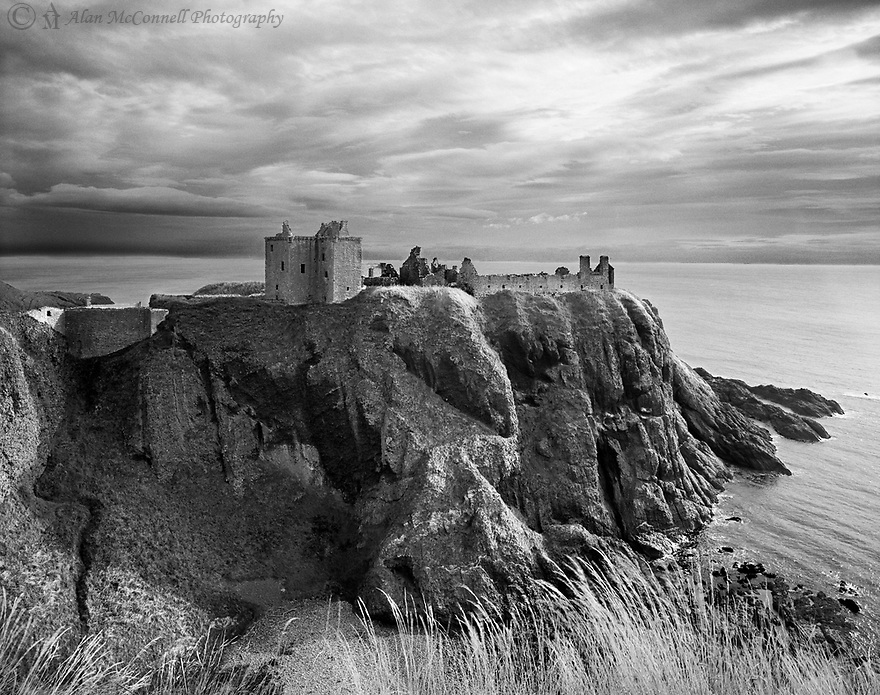 """Dunnottar Castle (Scottish Gaelic :Dùn Fhoithear, """"fort on the shelving slope"""") is surrounded by steep cliffs looking over the North Sea.  This medieval fortress is located about 2 miles south of Stonehaven, Scotland and is the subject of a long and often brutal history."""