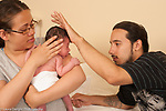 Newborn baby boy 1 week old with his parents, checking baby's forehead for temperature