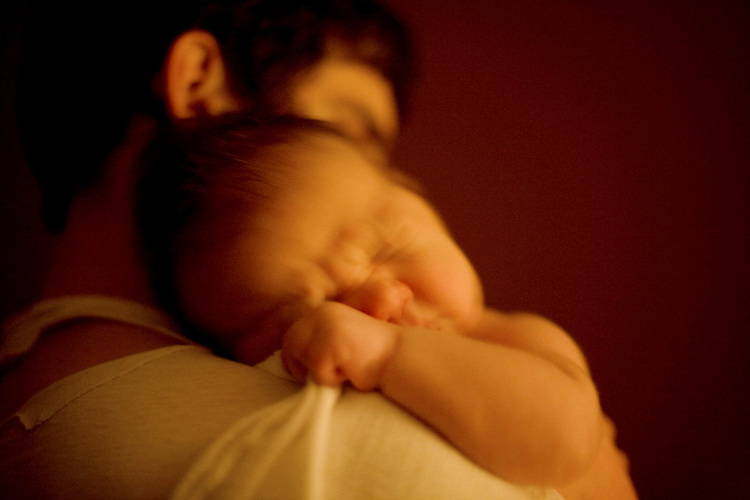 My younger son, then less than six weeks old, burrows into my husband as he brings the baby to me for a late-night nursing.