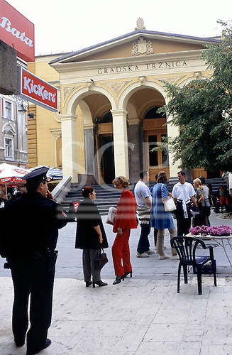 Sarajevo, Bosnia. Market hall and policeman in the city centre with Kickers and Bata advertisements.