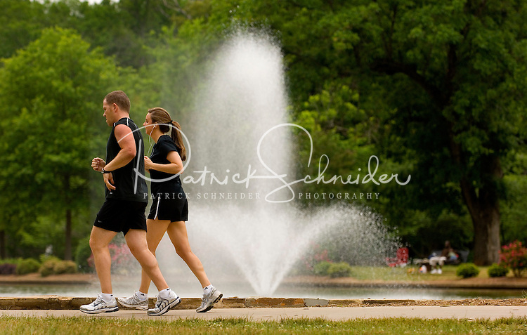 A couple runs past a fountain at Freedom Park in the Myers Park neighborhood in Charlotte, NC. Myers Park is one of the premier neighborhoods in North America and known for its large canopy of trees.