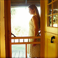 Looking through screen door at woman standing on porch<br />