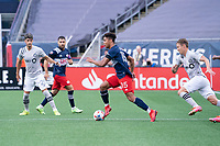 FOXBOROUGH, MA - JULY 25: Brandon Bye #15 of New England Revolution brings the ball forward with Lassi Lappalainen #21 of CF Montreal in pursuit during a game between CF Montreal and New England Revolution at Gillette Stadium on July 25, 2021 in Foxborough, Massachusetts.