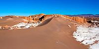 Beautiful, red Atacama Desert dunes and rocks surrounded by salt in El Valle de la Luna (Moon Valley) under a blue sky, San Pedro de Atacama, Chile