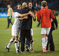The USA's  (left to right) Steve Cherundolo, head coach Bob Bradley, and Carlos Bocanegrao celebrate defeating Algeria 1-0 to win Group C and advancing to the second round of the 2010 FIFA World Cup.  USA played Algeria in a 2010 FIFA World Cup first round match at Loftus Versfeld Stadium in Tshwane/Pretoria, South Africa on Wednesday, June 23, 2010.