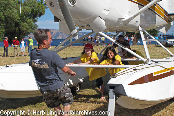 The volunteer Sea Scouts help Chris Brown reposition his turbo Cessna 206, TU206G, N247CB, at the Clear Lake Seaplane Splash-In, Lakeport, Lake County, California