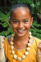 Polynesian girl wearing aloha wear with kukui nut lei. Smiling head and shoulders shot.