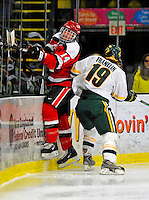 3 January 2009: St. Lawrence Saints' defenseman Jeff Caister (14), a Junior from Mississauga, Ontario, is checked into the boards by Josh Franklin of the University of Vermont Catamounts during the championship game of the Catamount Cup Ice Hockey Tournament at Gutterson Fieldhouse in Burlington, Vermont. The Cats defeated the Saints 4-0 and won the tournament for the second time since its inception in 2005...Mandatory Photo Credit: Ed Wolfstein Photo