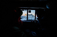 Two climbers look through the window of the old Perroux Hut, Chamonix, Alps, Mont Blanc Massif, France