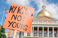 """A person holds a sign reading """"My kids / not yours"""" as people gather outside the Massachusetts State House for the No Mandatory Flu Shot MA demonstration in Boston, Massachusetts, on Sun., Aug. 30, 2020. The protest was organized in opposition to a newly-enacted law requiring most children in Massachusetts to receive flu vaccines this year as part of public health efforts during the ongoing Coronavirus (COVID-19) global pandemic. Some of those involved in this protest have been involved in the right-wing pro-Trump, pro-reopening protests organized by Super Happy Fun America during spring and summer 2020."""