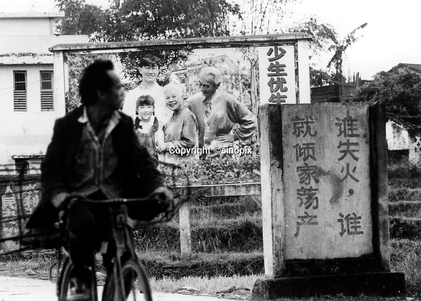 "A cyclist passes a propaganda poster that lets villagers know the  benifits of the One Child Policy"" in Huaji County. The One Child Policy has been used as a stick to extort fines from the farmers. The poverty gap in China is a major theme at this years National Perople's Congress in Beijing since it is causing destabilisation of the country as farmers sick of corrupt official take matters into their own hands.<br /> 25 Mar 2005<br /> <br /> photo by Richard Jones / Sinopix"