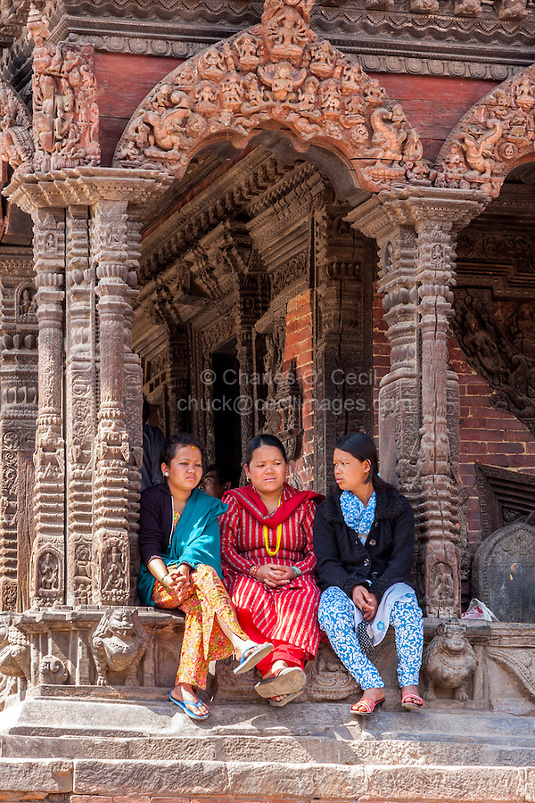Nepal, Patan.  Three Nepali Women Talking in the Shade of Vishwanath Temple,  Durbar Square.  The temple survived the earthquake of April 2015.