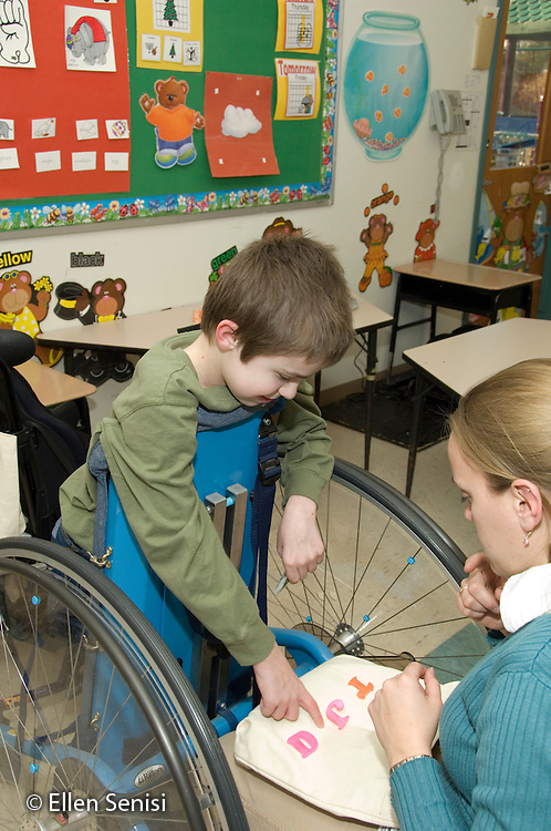 MR / Albany, NY.Langan School at Center for Disability Services .Ungraded private school which serves individuals with multiple disabilities.Child using Mobile Prone Stander identifies alphabet letters for his teacher. Boy: 10, Duchenne muscular dystrophy, expressive and receptive language delays.MR: Bud2; Ris4.© Ellen B. Senisi