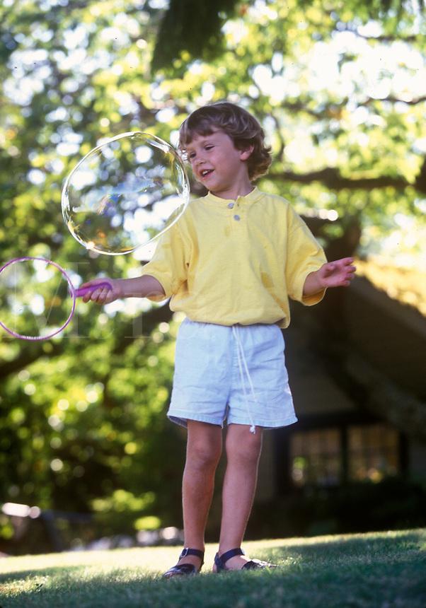 Young boy enjoys making bubbles.