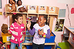 Education Preschool two girls in famiy area playing interactively talking and laughing