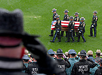 Police salute as the casket containing the remains of Connecticut State Police trooper Kevin Miller is brought onto the football field during the funeral ceremony, Friday, April 6, 2018, at Pratt and Whitney Stadium in East Hartford. (Jim Michaud / Journal Inquirer)