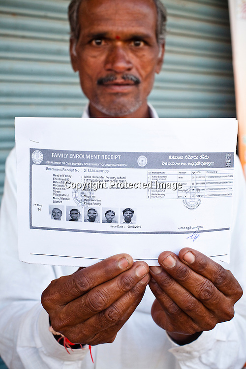 A villager shows the family enrollment slip outside the enrollment centre in Naagaaram village, outskirts of Hyderabad in Andhra Pradesh, India. India is assigning each one of its 1.2 billion people a unique ID number based on digital finger prints and iris scan. Photograph: Sanjit Das/Panos