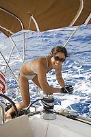 Young Asian local woman in bikini grinding winch while sailing a yacht off Hawaii