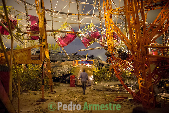 A man walks under the wreckage of a fair ride after a tornado ripped through a funfair in Gandia, near Valencia on September 29, 2012.  At least eight people, including a young girl and an elderly woman, have died in Spain as a result of floods brought on by downpours, regional officials said. Four people died in the Andalusia region, including a woman in her 80s, a couple found in their car and a man who died of a heart attack. Some 500 people remained evacuated from their homes in the area early on Saturday after the torrential rains caused rivers to break their banks and flooded roads and railways, regional authorities said. © Pedro ARMESTRE