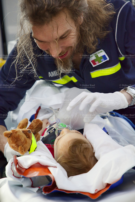 Switzerland. Canton Ticino. Lugano. A paramedic takes care of an injured child lying down on stretcher during an emergency medical ride by ambulance. The baby boy fell at home, hurt his head and is brought to hospital for a medical examination. The  paramedic is a professional certified nurse, wearing a blue uniform medical gloves. He works for the Croce Verde Lugano. The bearded paramedic smiles, talks to the child and shows him a brown stuffed bear. The Croce Verde Lugano is a private organization which ensure health safety by addressing different emergencies services and rescue services. Medical gloves are made of different polymers including latex, nitrile rubber, polyvinyl chloride and neoprene. 14.01.2018 © 2018 Didier Ruef