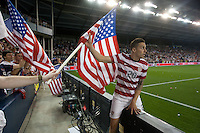 Geoff Cameron grabs a USA flag from an American fan after the United States Men's National Team's won its World Cup Qualifier against Guatemala 3-1 at Livestrong Sporting Park in Kansas City, Kansas on Tue. Oct. 16, 2012.