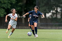 NEWTON, MA - AUGUST 29: Lucy Cappadona #4 of University of Connecticut brings the ball forward as Samantha Agresti #15 of Boston College closes during a game between University of Connecticut and Boston College at Newton Campus Soccer Field on August 29, 2021 in Newton, Massachusetts.