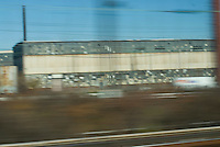 Factory Building in Industrial area viewed from window of moving passenger train, Central New Jersey, USA