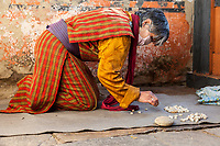 Bumthang, Bhutan.  Old Woman Praying.  Small Stones Help her Keep Track of the Number of Prostations.  Jambay Lhakhang Monastery.