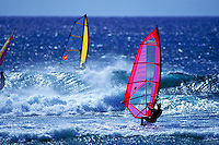 "Three windsurfers race against huge waves at """"Backyards"""", Sunset Beach on the famous north shore of Oahu."