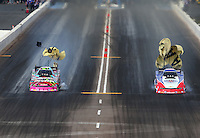 Feb 22, 2015; Chandler, AZ, USA; NHRA funny car driver Robert Hight (right) races alongside teammate Courtney Force during the Carquest Nationals at Wild Horse Pass Motorsports Park. Mandatory Credit: Mark J. Rebilas-