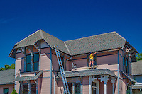 Worker installs new gutters at Flowers by Doris where construction began restoring the old home.