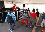 Justin Thistle, with justincredibledj.com, entertains students at the 10th annual Holiday with a Hero event at Walmart in Carson City, Nev., on Wednesday, Dec. 17, 2014. The event pairs 200 of Carson City's K-5th grade homeless students with a local heroes for Christmas shopping. <br /> Photo by Cathleen Allison