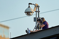 Charlotte Knights team photographer Laura Wolff gets the shot from the roof of Truist Field during the NCAA baseball game between the North Carolina Tar Heels and the South Carolina Gamecocks on April 6, 2021 in Charlotte, North Carolina. (Brian Westerholt/Four Seam Images)