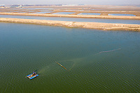 A fisherman trawls for fish on aquaculture farmland near the city of Huanghua, south of Tianjin. This area of coastline has been identified as being particularly vulnerable to coastal erosion on will increasingly be threatened as sea levels rise and storm surges increase. 2019