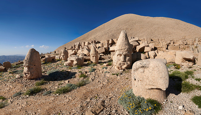 Statue head, from froint, of an eagle, Herakles & Apollo, & Zeus (left), in front of the stone pyramid  62 BC Royal Tomb of King Antiochus I Theos of Commagene, west Terrace, Mount Nemrut or Nemrud Dagi summit, near Adıyaman, Turkey