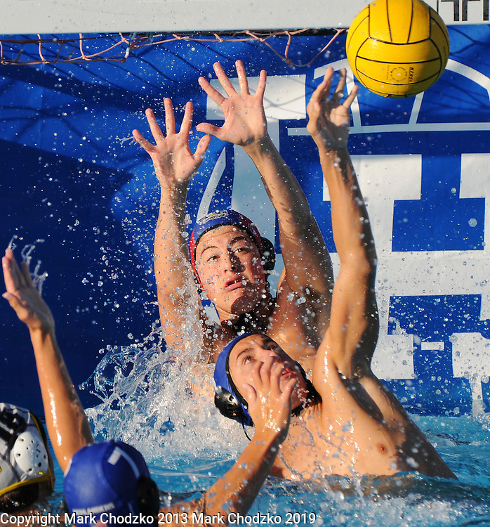 Boys High School water polo. Goalie tries to make a stop with a little help from his friends. sports, action, athletes, crowds