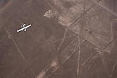 Nazca, Peru. Nazca Lines; aerial view of the flower geoglyph with a light aircraft passing over it.