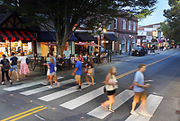 ALTERED STATE PHOTO ESSAY/ANDREW SHURTLEFF<br /> People cross the street on The Corner adjacent to the University of Virginia.<br /> <br /> Shut downs and stay-in-place orders, the most recent of which came from Gov. Ralph Northam Monday, have left Charlottesville dormant. Students have been sent home, many businesses have shut their doors and events have been canceled. In this photo essay, photographer Andrew Shurtleff has spent time capturing the effects of the pandemic and comparing the duality of the present with our social past.