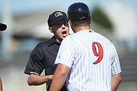 Home plate umpire Matt Baldwin explains his decision as Kannapolis Intimidators manager Justin Jirschele (9) argues a call that was reversed during the game against the Greensboro Grasshoppers at Kannapolis Intimidators Stadium on August 5, 2018 in Kannapolis, North Carolina. The Intimidators defeated the Grasshoppers 9-0 in game two of a double-header.  (Brian Westerholt/Four Seam Images)