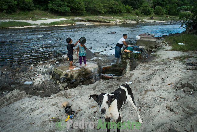 """November 07, 2014. """"Water it´s the real thing""""<br /> The family  of Edwin Salguero wash in Acelhuate river (Nejapa, El Salvador) because they don' t have drinking water at home. The river is contaminated. Edwin and his family have to walk near two hours to get the river. <br /> The people of Nejapa in El Salvador, have no drinking water because the Coca -Cola company overexploited the aquifer in the area, the most important source of water in this Central American country. This means that the population has to walk for hours to get water from wells and rivers. The problem is that these rivers and wells are contaminated by discharges that makes Coca- Cola and other factories that are installed in the area. The problem can increase: Coca Cola company has expansion plans, something that communities and NGOs want to stop. To make a liter of Coca Cola are needed 2,4 liters of water. ©Calamar2/ Pedro ARMESTRE"""