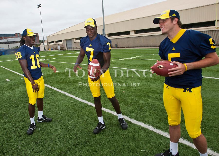 Michigan quarterbacks Denard Robinson (16), Devin Gardner (7), and Tate Forcier (5) juggle footballs, at the annual NCAA college football media day, Sunday, Aug. 22, 2010, in Ann Arbor, Mich. (AP Photo/Tony Ding)