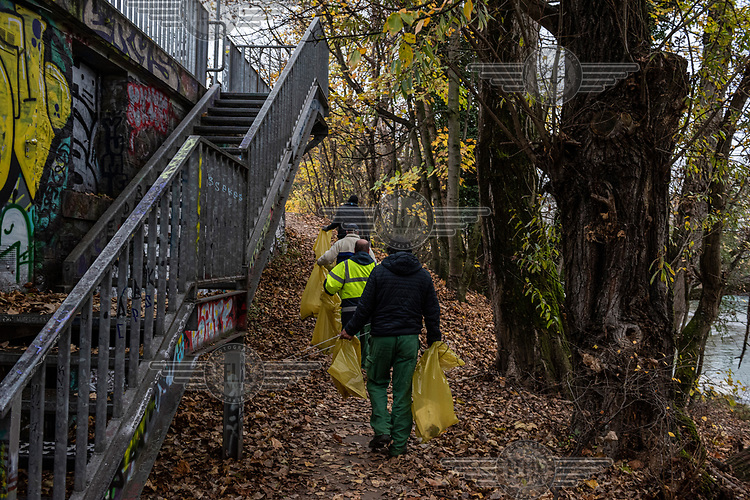 A council cleaning squad walk along the Arve River. They have removed some old mattresses used by homeless people but left those that had been carefully hidden and therefore definitely in  use. A number of people are sleeping rough beside the river, and under its bridges, hidden from most people's view.