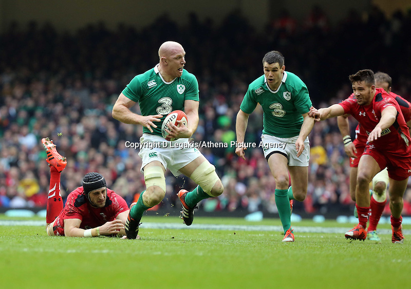 Pictured: Paul O'Connell of Ireland (2nd L) is tripped up by Luke Charteris of Wales (L) Saturday 14 March 2015<br /> Re: RBS Six Nations, Wales v Ireland at the Millennium Stadium, Cardiff, south Wales, UK.