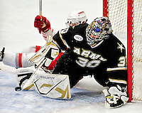 2 January 2011: Army Black Knight goaltender Ryan Leets, a Sophomore from Kentwood, MI, makes a save as Ohio State University Buckeye forward Danny Dries, a Junior from  Lake Orion, MI, slides into the net, knocking it off its mooring at Gutterson Fieldhouse in Burlington, Vermont. The Buckeyes defeated the Black Knights 5-3 to win the 2010-2011 Catamount Cup. Mandatory Credit: Ed Wolfstein Photo