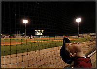 A young boy turns his attention to blowing spit bubbles rather than the action on the field while attending a Kannapolis Intimidator's game from behind the nets. Boy is model released.
