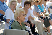 An elderly woman sings along with a music hall performance at Church Street Summer Festival 2005, Paddington, London.