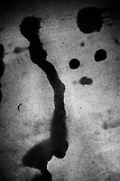 Switzerland. Canton Ticino. Viganello. Car's gear and motor oil leaks on the ground. Silhouette 's face. Two eyes and a nose. Viganello is a quarter of Lugano. 23.05.2020 © 2020 Didier Ruef